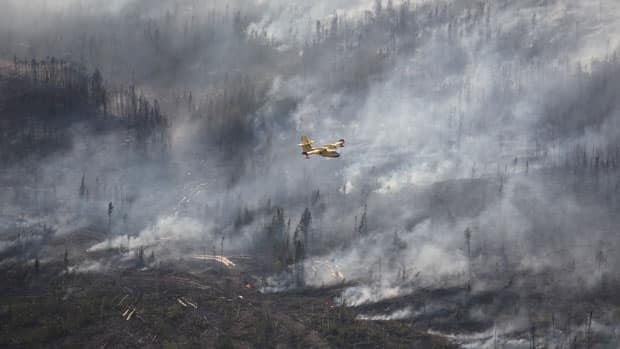 A water-bomber flies over a forest fire located near Kirkland Lake, Ont.