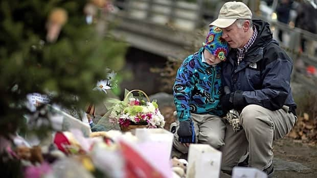 David Freedman, right, kneels with his son, Zachary, 9, as they visit a sidewalk memorial for the Sandy Hook Elementary School shooting victims in Newtown, Conn. Experts encourage parents to talk to their kids about Friday's mass shooting.