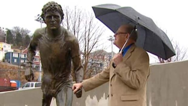 Rolly Fox holds the hand on a statue of his son, Terry Fox, soon after its unveiling in St. John's in 2012.