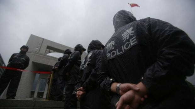 Police officers stand guard at the Hefei City Intermediate People's Court for the murder trial of Gu Kailai, wife of ousted Chinese politician Bo Xilai, on Thursday.