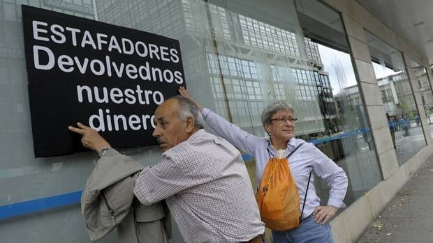 Two protestors stick a placard reading 'Thieves, give us our money back' on a bank office during a demonstration against bank fraud in Coruna on June 2. There are growing fears a bailout of Spanish banks may not be enough to save the country from economic chaos.