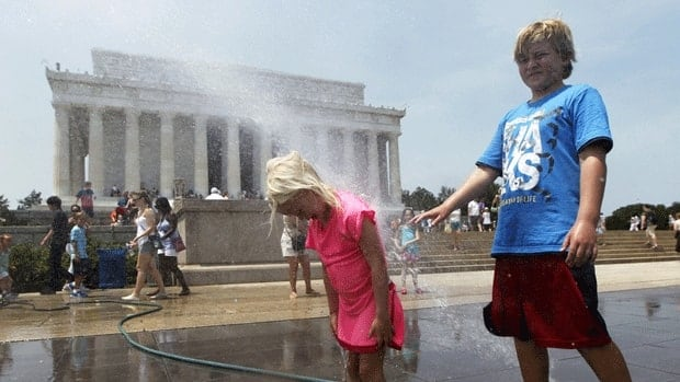 Children cool themselves with a spray of water leaking from a hose outside the Lincoln Memorial on the Washington Mall, where temperatures hovered around 38 C.