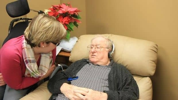 Jimmy Andrew, 83, a resident at The Village at Wentworth Heights, listens to music on his iPod with recreation therapist, Kristel Balthuis. She uses music to help treat and bring joy to elderly patients who experience dementia or have withdrawn socially.
