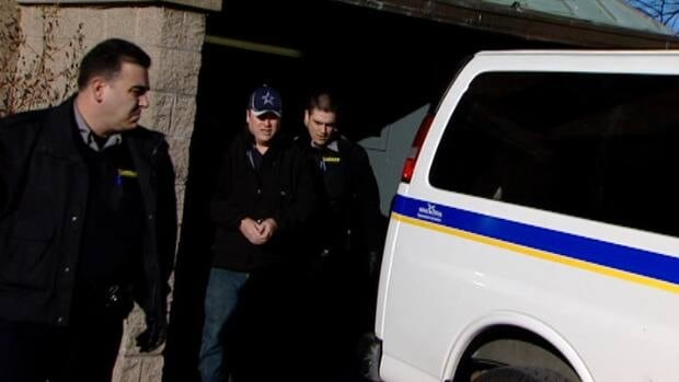 Canadian naval intelligence officer Jeffrey Paul Delisle, centre, is led out of court Monday. Delisle pleaded guilty under the Security of Information Act of passing secrets to a foreign entity.