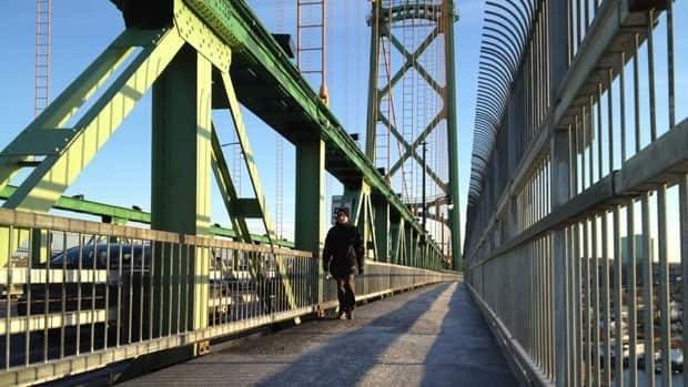 A pedestrian crosses the Angus L. Macdonald Bridge Monday morning.