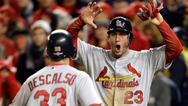 St. Louis Cardinals' David Freese, right, reacts as he and Daniel Descalso score on a single by Pete Kozma in the ninth inning of Game 5 of the NLDS.