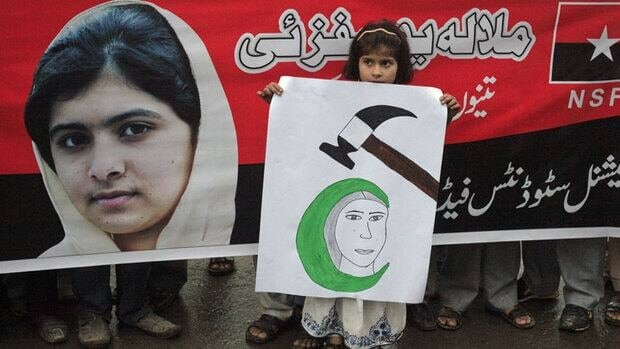 A girl at a rally organized by the National Students Federation in Lahore, Pakistan, holds a placard next to an image of Pakistani schoolgirl and education activist Malala Yousufzai, who was shot on Oct. 9 by the Taliban and influenced people around the world to support her fight for girls' education.