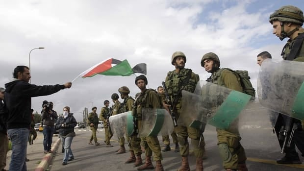 A Palestinian waves a national flag in front of Israeli soldiers during a protest against the building of settlements at Gush Etzion junction, near the West bank town of Bethlehem on Nov. 9.