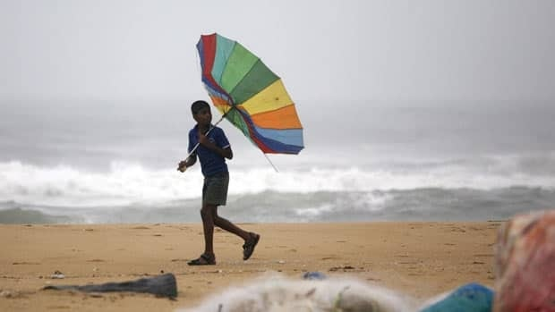 An Indian boy tries to hold his umbrella on Tuesday against strong winds as he walks the Bay of Bengal coast in Chennai, India.