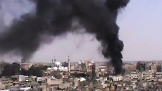 This image made from amateur video provided by the Shaam News Network and accessed Monday, purports to show black smoke rising from buildings in Homs, Syria, after military forces renewed shelling of the city.