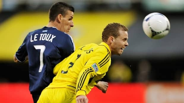 Josh Williams of the Columbus Crew, right, beats Sebastien Le Toux of the Vancouver Whitecaps to the ball in the first half on April 28, 2012.