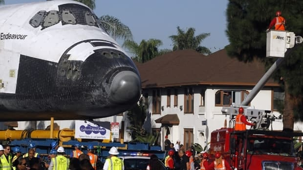 Tree trimmers do last minute work to make room for the Space Shuttle Endeavour during the final leg of a journey to it's new permanent home at the California Science Center in Exposition Park in Los Angeles, California, October 14, 2012.