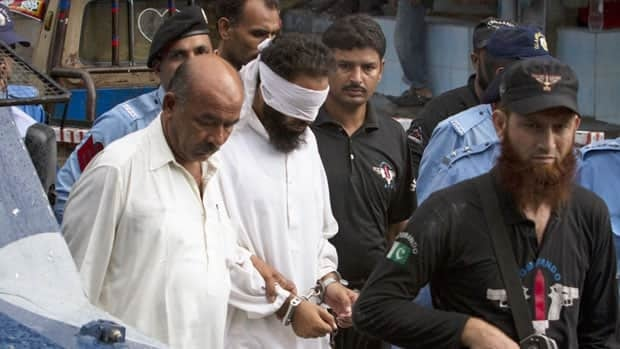 Police escort blindfolded Muslim cleric Khalid Jadoon as he is brought before a judge at a court in Islamabad on Sunday.