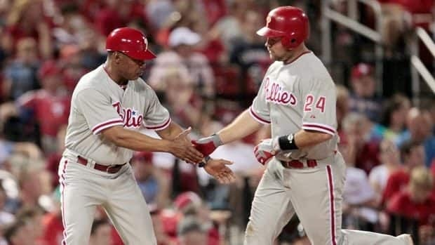 Philadelphia Phillies' Ty Wigginton, right, is congratulated by third base coach Juan Samuel while rounding the bases after hitting a solo home run during the eight inning against the St. Louis Cardinals Thursday.