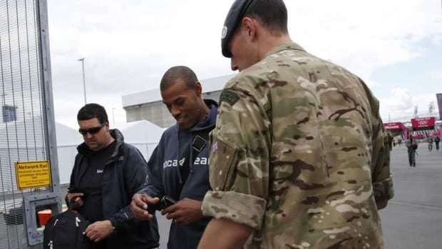 A British soldier checks ID cards at the entrance to Olympic Park in London. The Summer Games begin July 27, but security preparations have hit several snags.