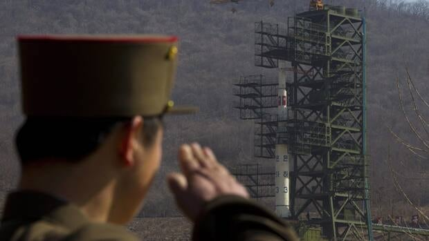 A North Korean soldier salutes in front of the country's Unha-3 rocket at Sohae Satellite Station in Tongchang-ri, North Korea. The country may postpone the controversial launch of a long-range rocket that had been slated for lift off as early as Monday.