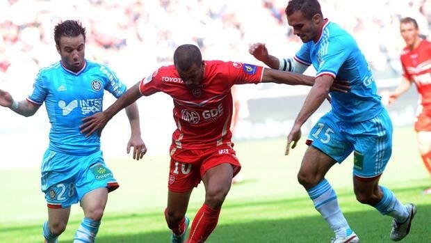 Valenciennes' midfielder Mathieu Dossevi, centre, vies with Marseille midfielder Mathieu Valbuena, left, and defender Jeremy Morel during their match Sunday.