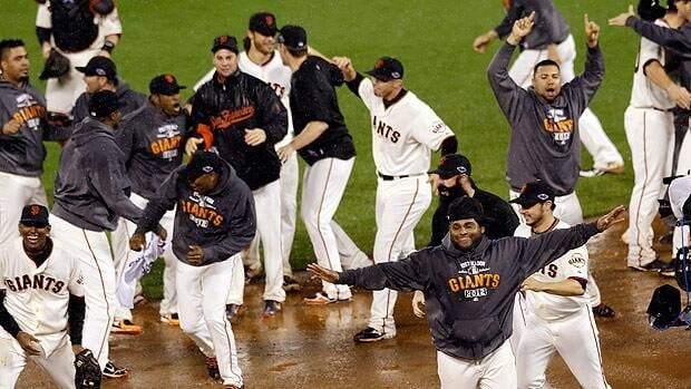 San Francisco Giants players celebrate during the downpour moments after the final out in Game 7 against St. Louis.