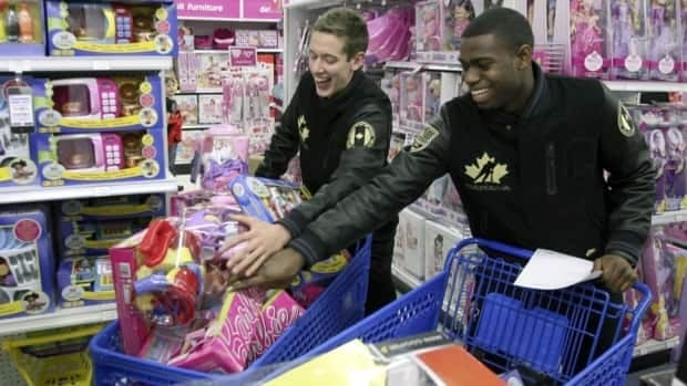 Canada's National Junior Team members Jordan Binnington, left, and Malcolm Subban, right, do their part to collect more than $10,000 worth of toys alongside their team members at Nike's Fuel A Charity event, Friday, December 14, 2012, in Calgary.
