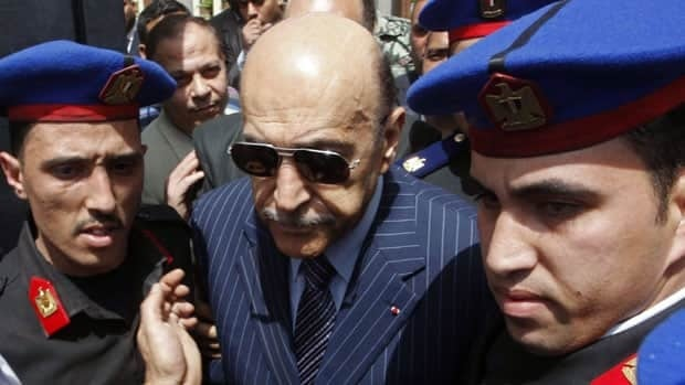 Egypt's former spy chief, Omar Suleiman, is escorted by police after he submitted his candidacy papers at the Higher Presidential Elections Commission in Cairo in April. Suleiman has died in the U.S. at age 76.
