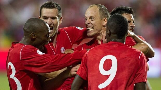 Canada's captain Kevin McKenna, centre, celebrates Atiba Hutchinson, left, David Edgar, centre-left, Tosaint Ricketts, centre-right, and Ante Jazic after Dwayne DeRosario (hidden) scored against Panama during the second half on Friday.