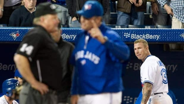 Toronto Blue Jays Brett Lawrie (right) looks back after being ejected from the game after contesting a strike out call, as Home Plate Umpire Bill Miller (left) is confronted by Jays Manager John Farrell during the ninth inning against Tampa Bay Rays in Toronto on Tuesday.