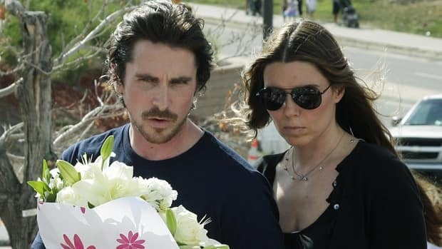 Actor Christian Bale and his wife Sibi Blazic carry flowers to place on a memorial to the victims of Friday's mass shooting.