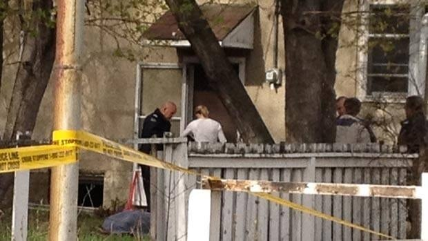 Firefighters and police investigate the discovery of a body following a house fire Tuesday morning.