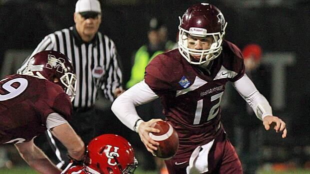 McMaster University Marauders quarterback Kyle Quinlan carries the ball past University of Calgary Dino's Lyndon Gaydosh during first half Mitchell Bowl football action in Hamilton.