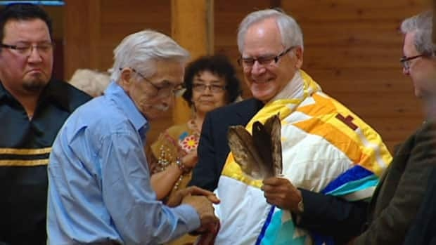Winnipeg Archbishop James Weisgerber is welcomed into the aboriginal community by local elders on Saturday, as part of a symbolic 'adoption' ceremony.