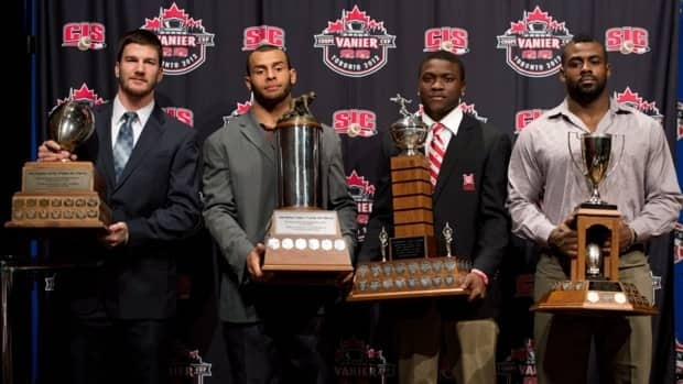 CIS award winners, McMaster University quarterback Kyle Quinlan, left, poses with the Hec Crighton trophy, Ben D'Aguilar, from McMaster University poses with the J.P.Metras trophy, Shaquille Johnson, from McGill Univeristy poses with the Peter Gorman trophy and Frederic Plesius, right, from Laval University poses with the President's trophy during the CFL awards in Toronto Thursday, November 22, 2012.