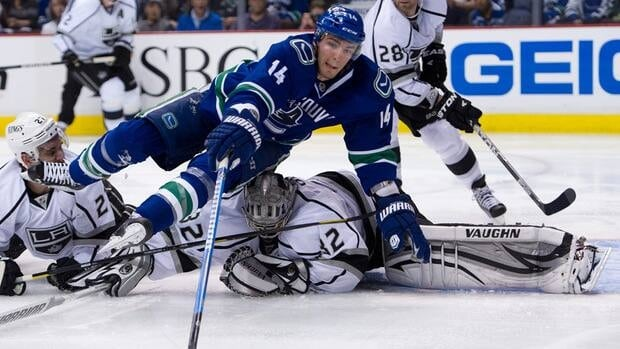 Alexandre Burrows of the Vancouver Canucks trips over goalie Jonathan Quick of the Los Angeles Kings while reaching for a loose puck in Game One of the Western Conference Quarterfinals during the 2012 NHL Stanley Cup Playoffs