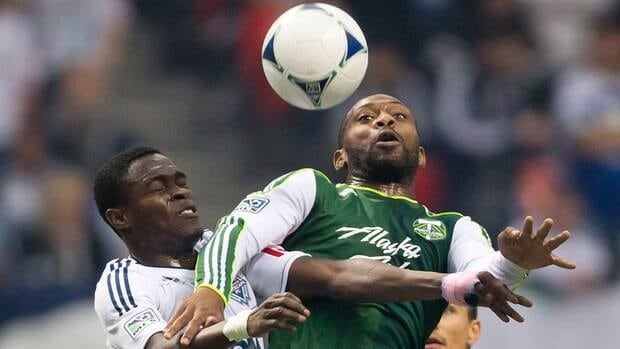 Vancouver Whitecaps' Gershon Koffie and Portland Timbers' Franck Songo'o vie for the ball in the first half of Sunday night's match between the two clubs.