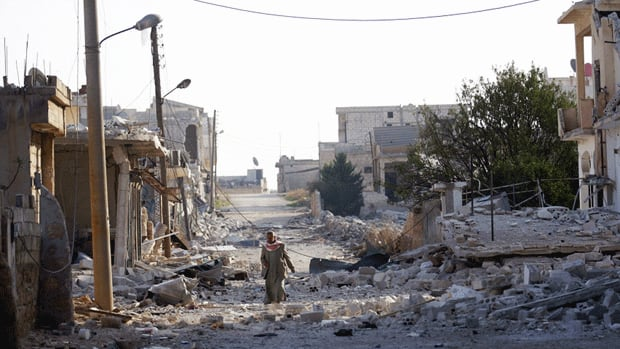 A Syrian man walks past destroyed buildings in the town of Taftanaz, on the outskirts of Idlib on Friday.