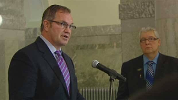 MLA Steve Young addresses reporters at the Alberta legislature on Monday, while Government House Leader Dave Hancock looks on.