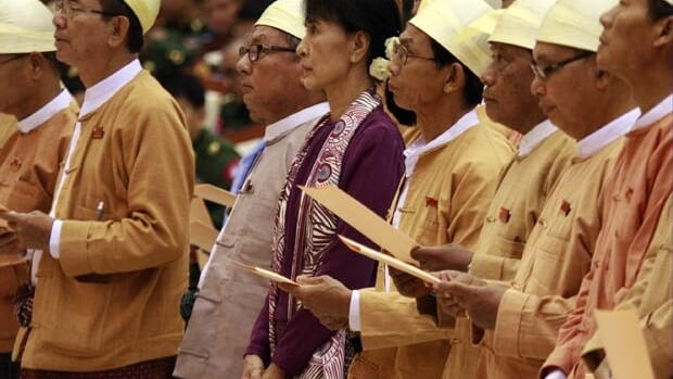 Burmese pro-democracy icon Aung San Suu Kyi, centre, and elected representatives of her National League for Democracy party are sworn in during a regular session at parliament in Naypyidaw, Wednesday.