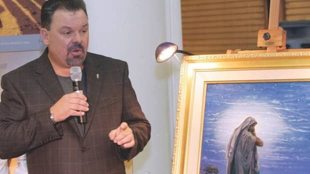 Thomas Kinkade is shown Sept. 15, 2006 with his painting, Prayer For Peace in Atlanta. He died April 6 at his California home. A dispute between his wife and his girlfriend over his estate has been settled.