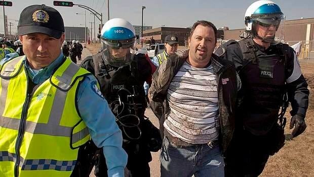 A laid-off Aveos employee is arrested during a demonstration in front of the aircraft maintenance company's plant Tuesday in Montreal. Workers took their case to Quebec's national assembly.