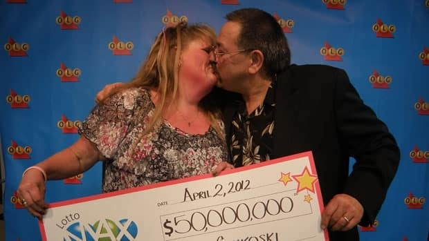 Jo-Anne and Louis Chikoski of Thunder Bay kiss after accepting a cheque for $50 million in Toronto after winning the Lotto Max jackpot.
