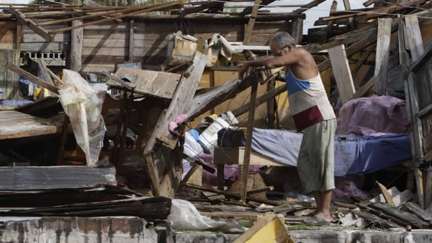 Resident Antonio Garces tries to recover his belongings from his house destroyed by Hurricane Sandy in Aguacate, Cuba.