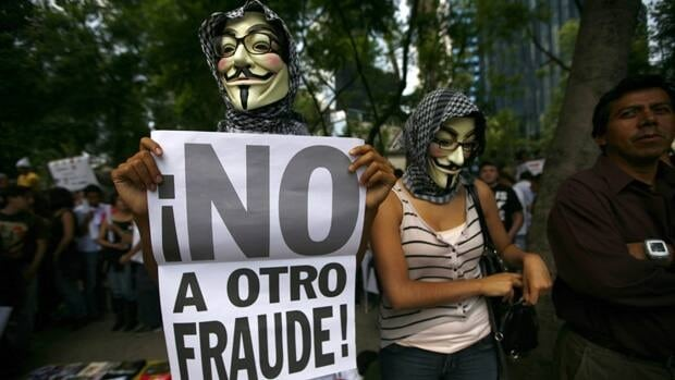 Wearing a Guy Fawkes mask, a Mexican unhappy with the presidential election result, holds a banner that reads in Spanish: No to another fraud!, during a march in Mexico City, Saturday. The protesters believe Pena Nieto's PRI party engaged in vote-buying that illegally tilted millions of votes. PRI officials deny the charge.
