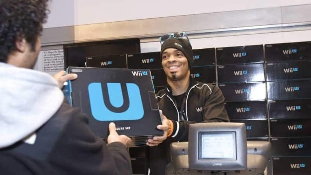 A fan purchases one of the first Wii U systems at the midnight launch event at Nintendo World in New York on Sunday. There have been reports that slow firmware updates may have led to trouble with some machines.