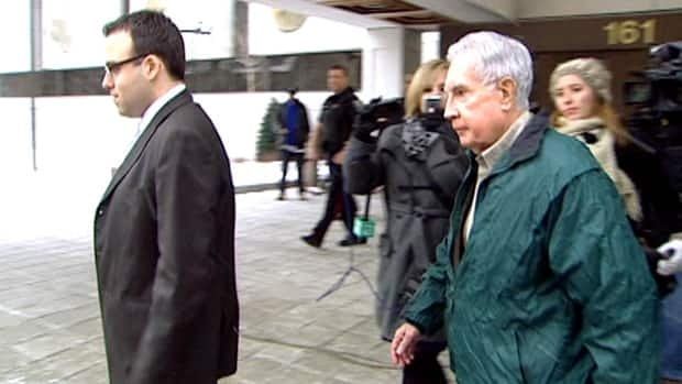 Raymond Lahey walks quickly past reporters after sentencing at an Ottawa courthouse.