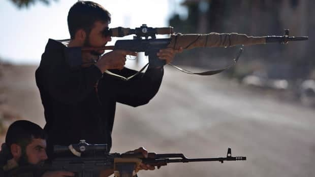 Syrian rebel snipers aim at Syrian army positions on the outskirts of Aleppo, Syria Wednesday. France has said it will ask the European Union to raise an embargo so it can send 'defensive arms' to rebel forces.