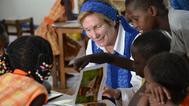 After writing an article for Reader's Digest about OSU Children's Library Fund founder Kathy Knowles, Deborah Cowley decided to volunteer for the project. Here she reads to some of the children.