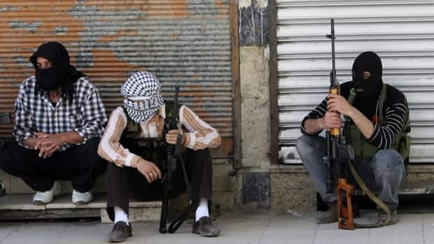 Anti-government soldiers sit by the side of a street in the Syrian capital of Damascus. UN-led peace efforts in the country have unravelled amid escalating violence.