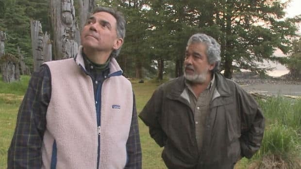 Former environment minister Jim Prentice, on the left, and Guujaaw, on the right, take in the totem poles at Sgang Gwaay at the Gwaii Haanas National Park Reserve in June 2010.