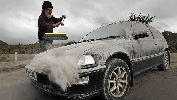 Vic Cassin sweeps ash from a car in Rangipo near Mount Tongariro, New Zealand after an volcanic eruption Tuesday.