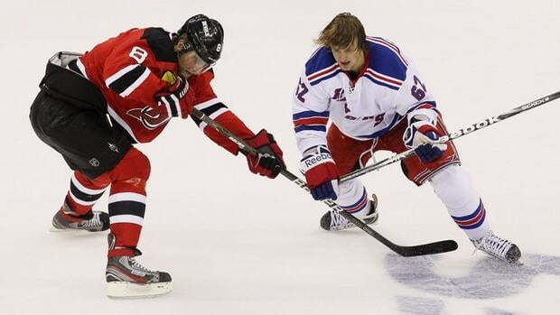 Dainius Zubrus of the New Jersey Devils, left, vies for the puck with Carl Hagelin of the New York Rangers in Game 4.