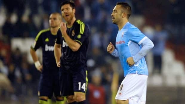Celta's midfielder Cristian Bustos, right, past Real Madrid's midfielder Xabi Alonso, centre, after scoring during the Spanish Copa del Rey at the Balaidos stadium in Vigo on Wednesday.